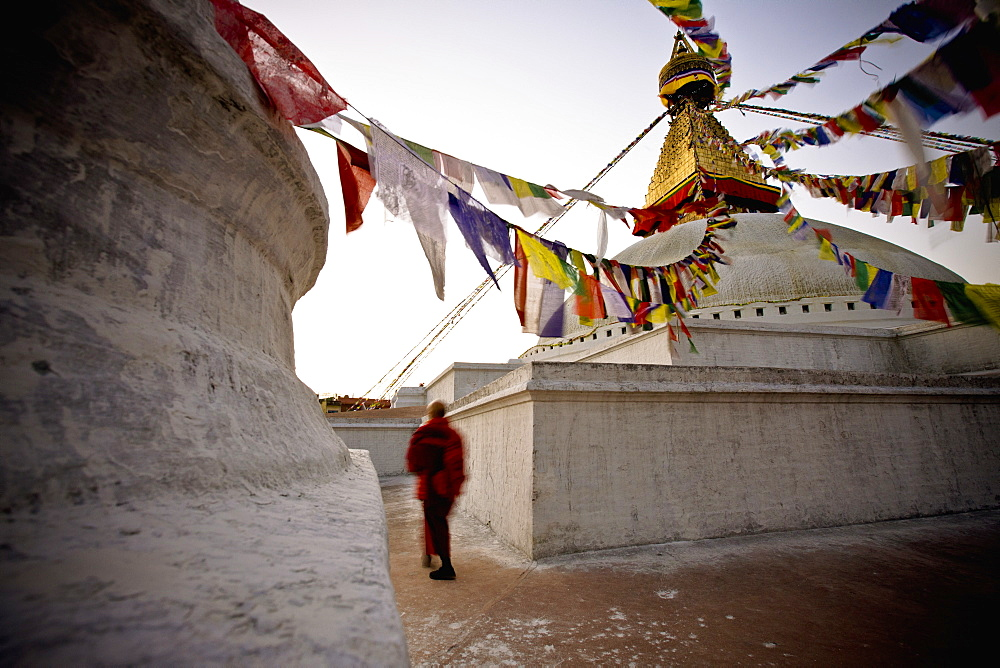 A Man Walking Amongst The Buildings With Prayer Flags Hanging Above, Kathmandu, Nepal