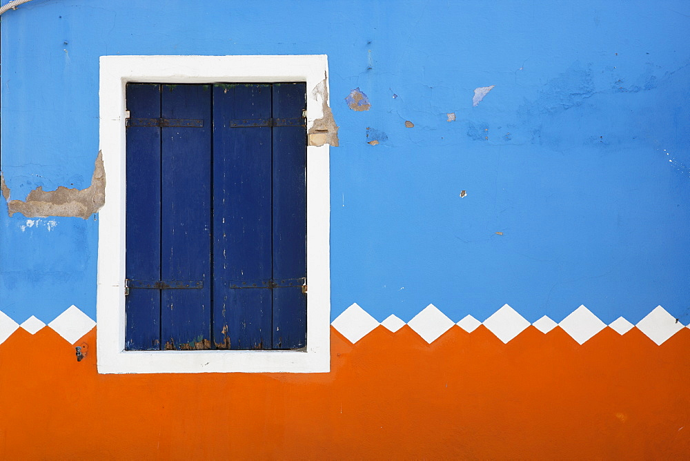 Paint Peeling Off Of A Decorative Exterior Wall And A Closed Shutters On A Window, Burano, Venezia, Italy