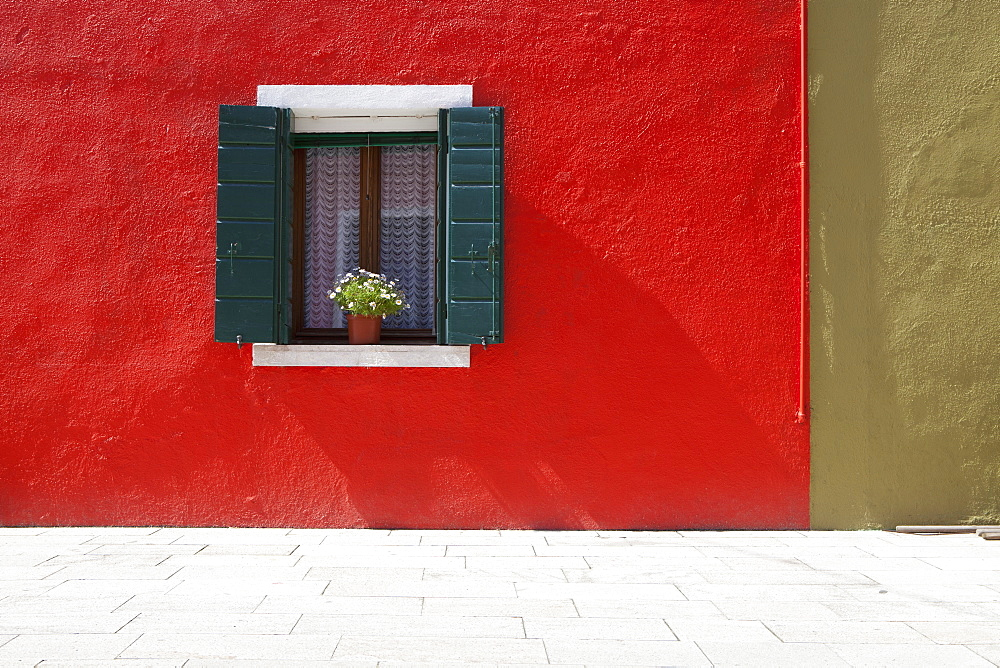 A Flower Pot Sits In A Window With Shutters Open In Building Painted Bright Red, Burano, Venezia, Italy