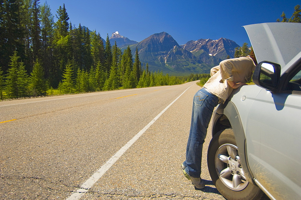 Woman Looking Under Hood Of Her Car On Mountain Road, Alberta Canada