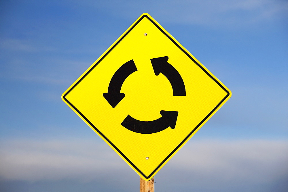 A Yellow Sign Showing Three Arrows Going In A Circle, Calgary, Alberta, Canada