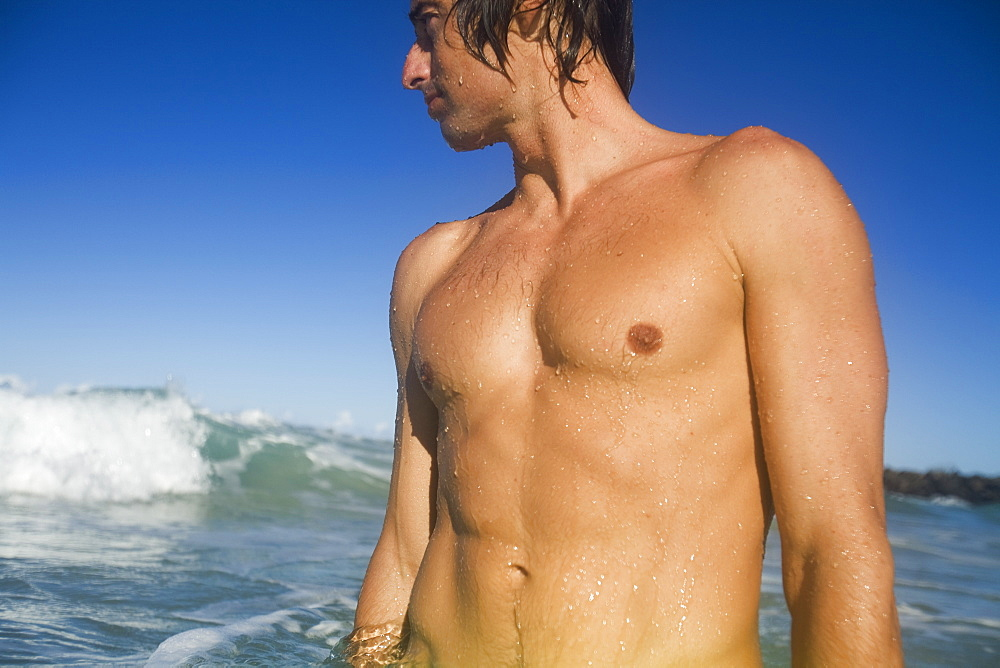 A Young Man Standing In Water Watching The Waves, Gold Coast, Queensland, Australia