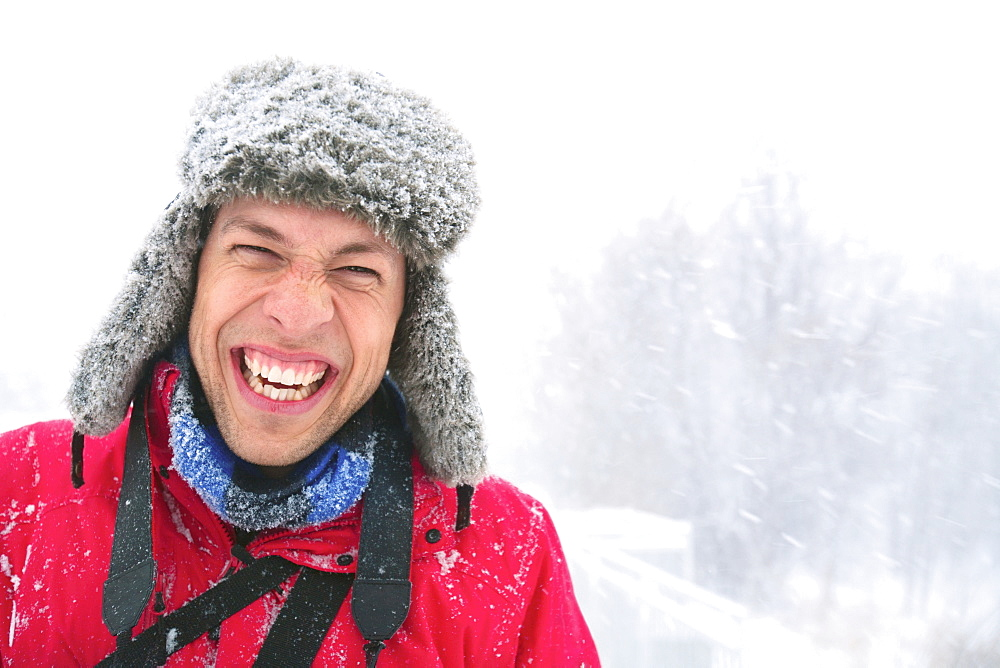 A Young Man Laughing A He Wears A Fur Hat Covered In Snow On A Snowy Day, Eagan, Minnesota, United States of America