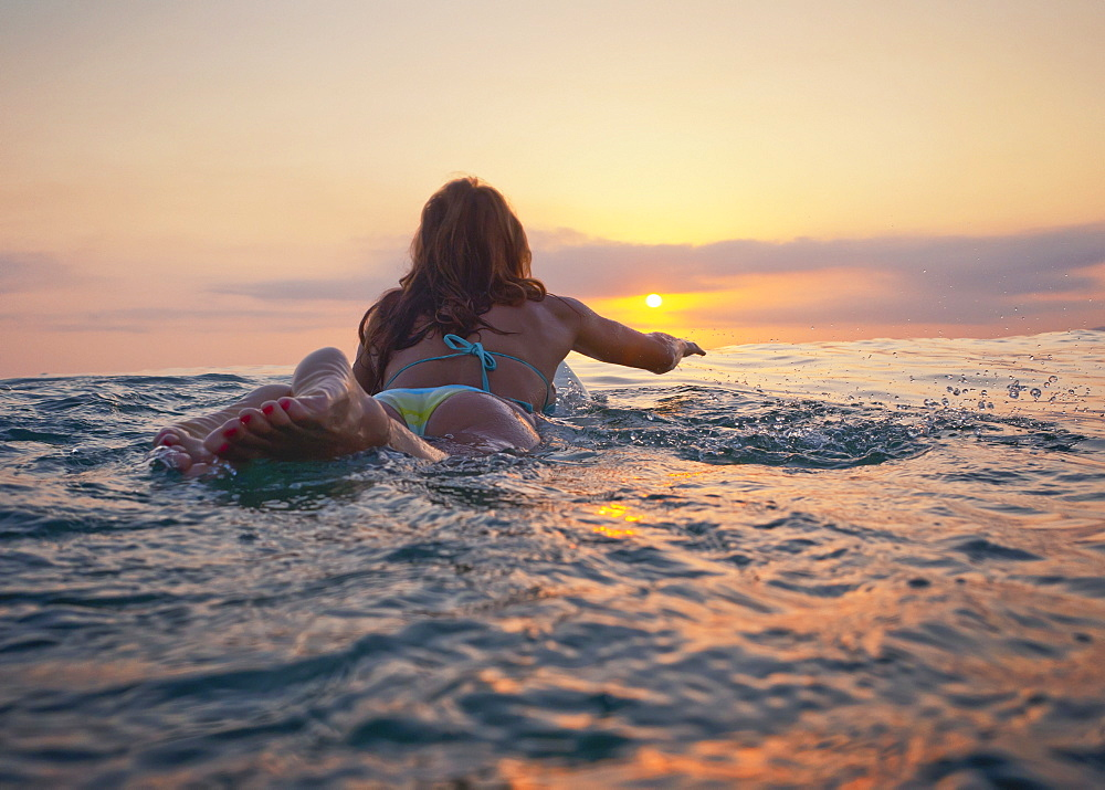 A Woman Laying On A Surfboard Watching The Sunset, Tarifa, Cadiz, Andalusia, Spain