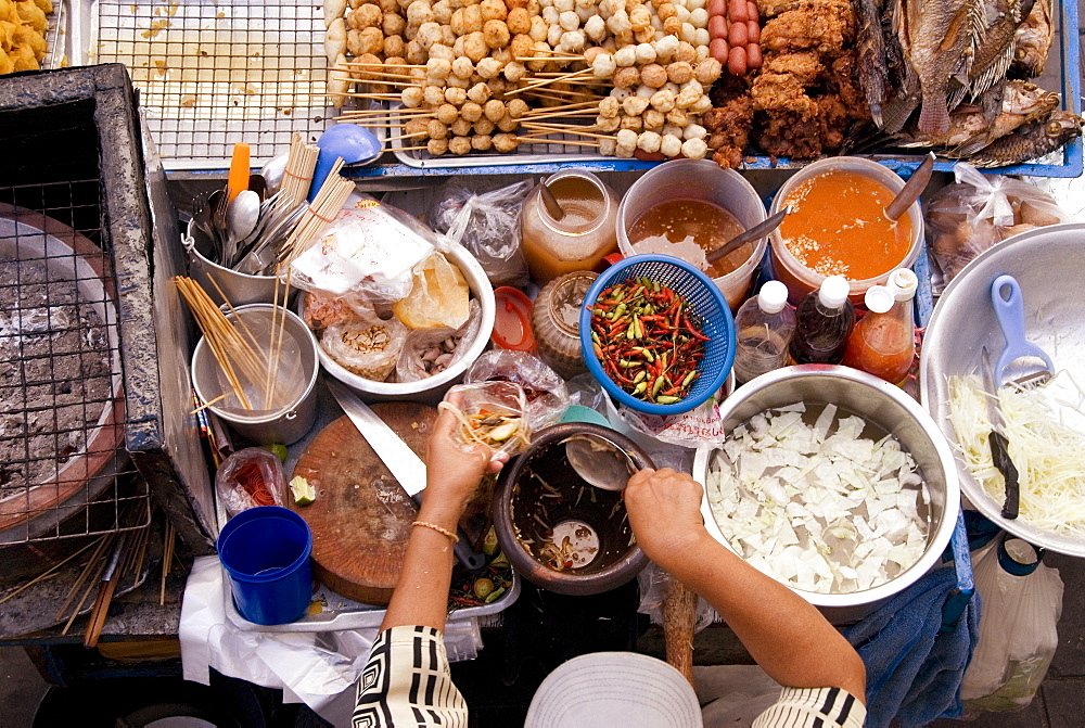 Thailand, Bangkok, View From Above Of A Street Food Stall With Vendor Prepping Food.