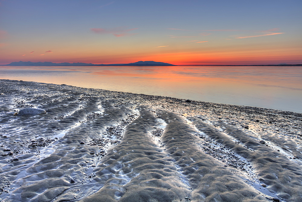 Ripples and patterns in the sand at the waters edge with a pink sunset on the horizon