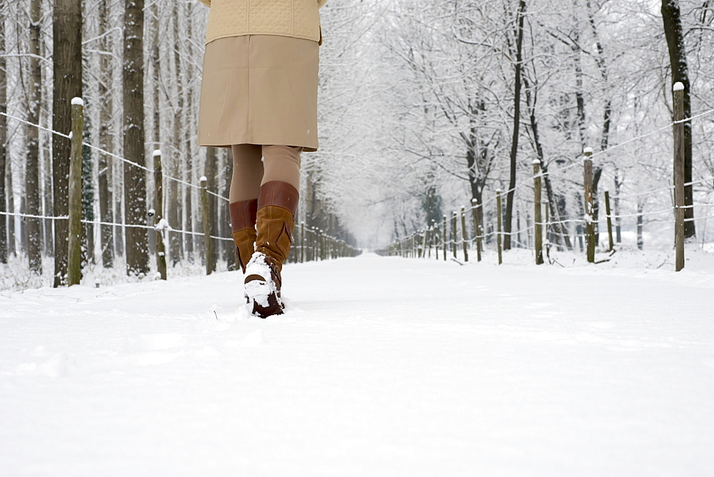A woman walks down a snowy path in winter, Locarno ticino switzerland