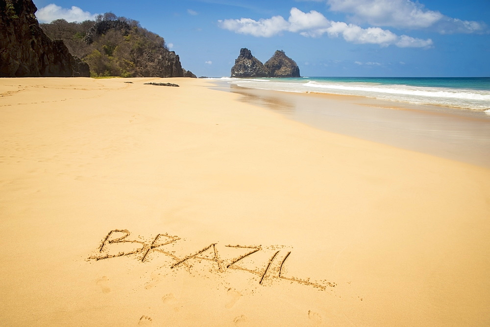 View of morro dos irmaos from praia do bode with brazil written in the sand, Fernando de noronha pernambuco brazil