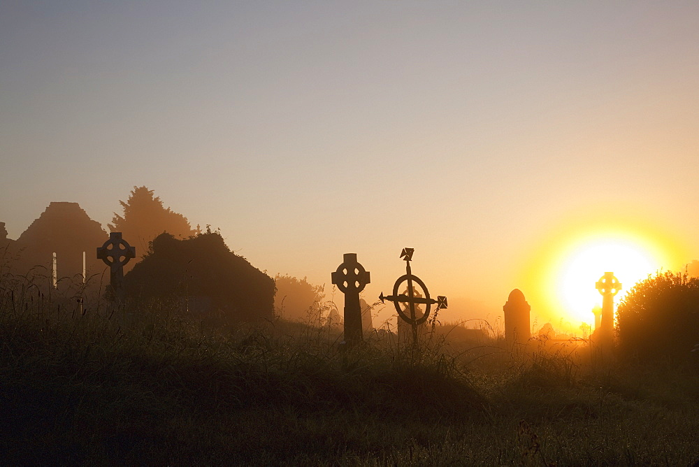 Sunrise at aghadoe heights graveyard with silhouetted tombstones, Killarney, county kerry, ireland
