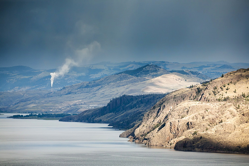 The dry hills of kamloops with a smokestack spewing pollution in the distance, Kamloops, british columbia, canada