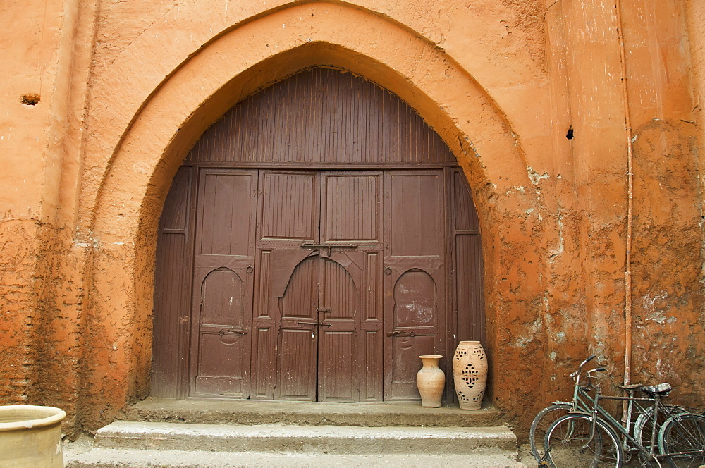 Wooden Door Of A House With An Archway And Two Bikes Parked Outside, Marrakech Morocco