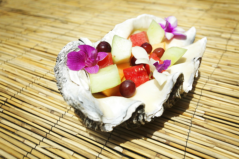 A Fruit Salad With Floral Garnishes Served Inside A Seashell, Hawaii United States Of America