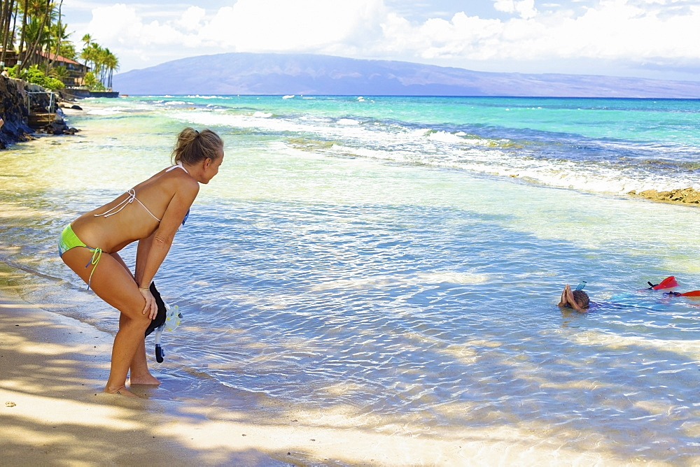 A mother watches her son snorkelling in the shallow water at the beach, Hawaii united states of america - 1116-41869