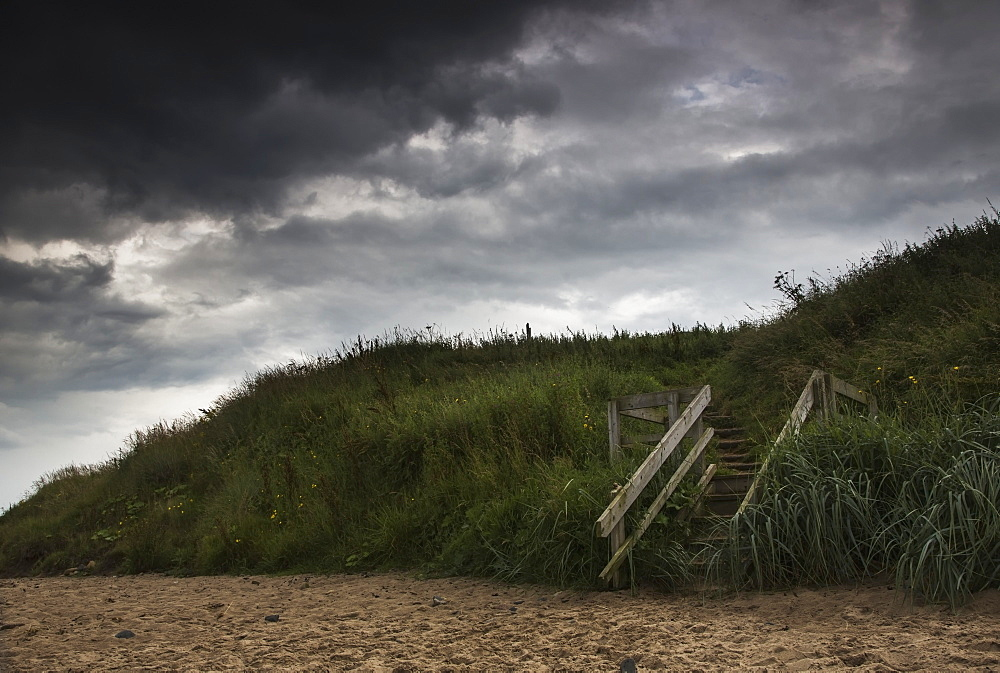 Wooden steps leading to the beach under dark storm clouds, Druridge bay northumberland england