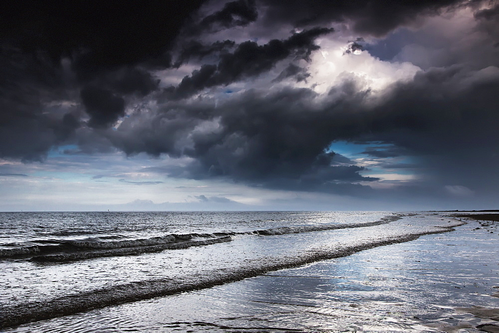 Dark storm clouds over the ocean with waves rolling into the shore, Druridge bay northumberland england