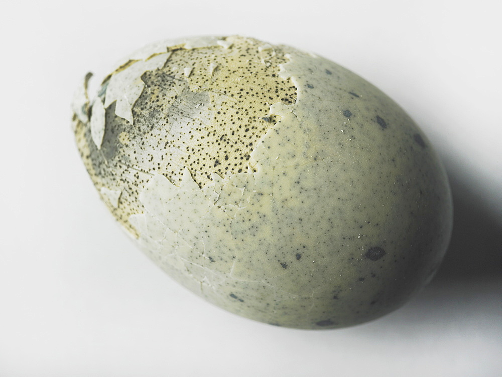 An egg with shell cracked on a white background