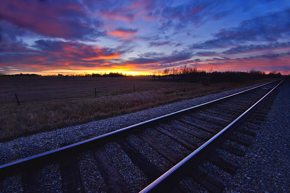 Train tracks and a dramatic colourful sky at sunset, Millet alberta canada