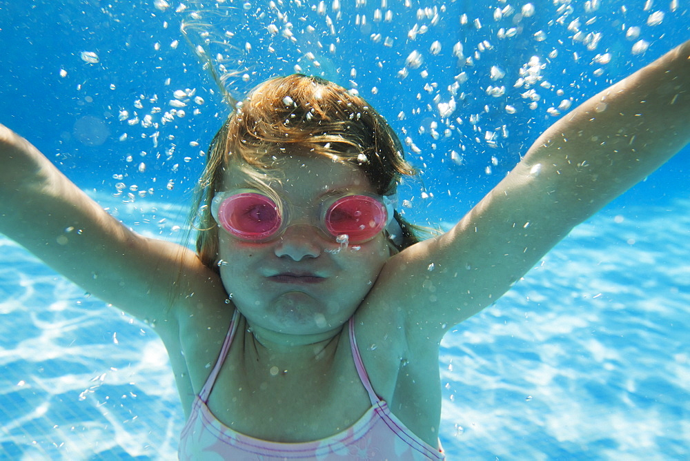 A girl swimming under the water in a pool with goggles on, Tarifa cadiz andalusia spain - 1116-41978