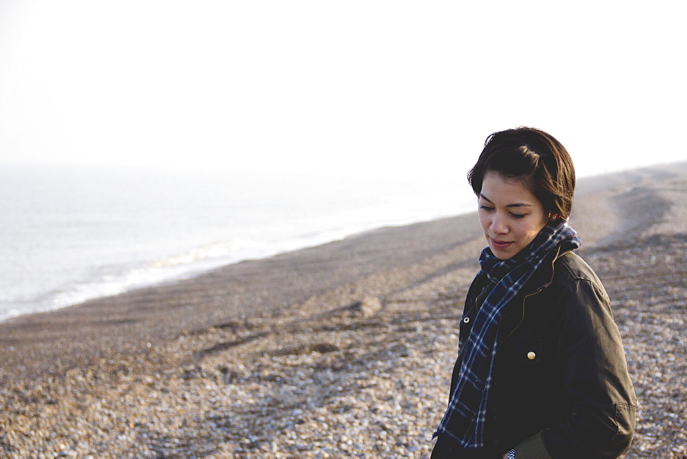 A Young Woman Stands On The Rocky Beach At The Water's Edge, Aldeburgh, England