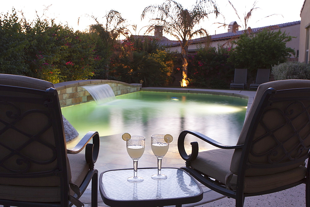 Pool Side Setting At Dusk With Pool Lights Two Chairs Table And Two Glasses With Lime Wedges, Palm Springs, California, United States of America
