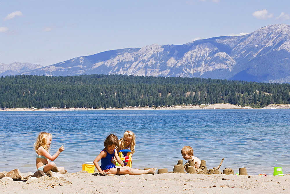 Children Playing On Beach On Lake Koocanusa In The East Kootenays Near Fernie, British Columbia, Canada