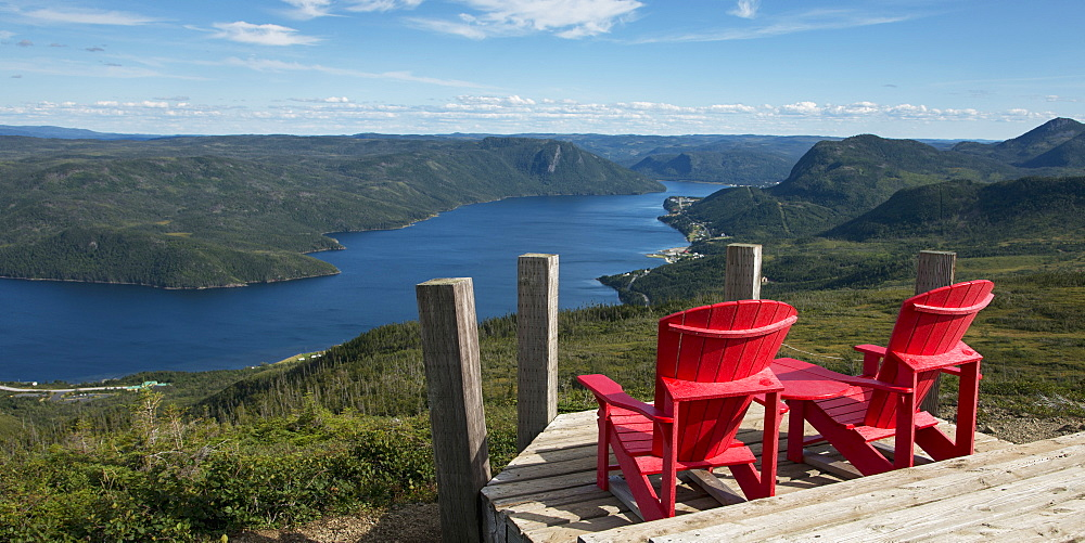 Two Red Adirondack Chairs On A Wooden Deck Overlooking Bonne Bay, Newfoundland And Labrador, Canada