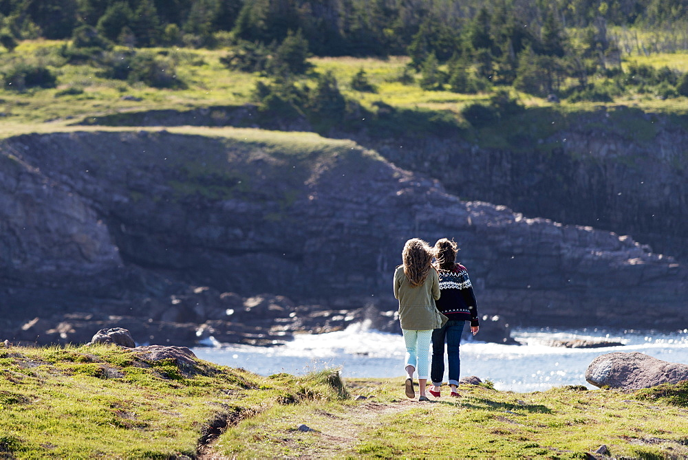 A Mother And Daughter Stand On A Trail Overlooking The Atlantic Coastline At Cape Spear, St. John's, Newfoundland And Labrador, Canada