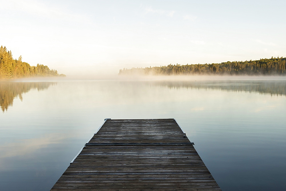 A Wooden Dock Leading Out To A Misty Tranquil Lake In Riding Mountain National Park, Wasagaming, Manitoba, Canada
