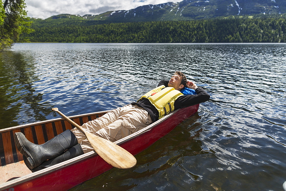 Man Reclined In Canoe And Resting In The Sunshine On Byers Lake With Forested Foothills In The Background, Byers Lake Campground, Denali State Park, Alaska, United States Of America