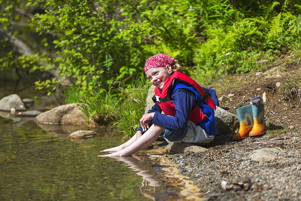 Young Girl Wearing A Lifejacket And Sitting On A Sun Drenched Shore Of Byers Lake Soaking Her Bare Feet In The Water, Byers Lake Campground, Denali State Park, Alaska, United States Of America