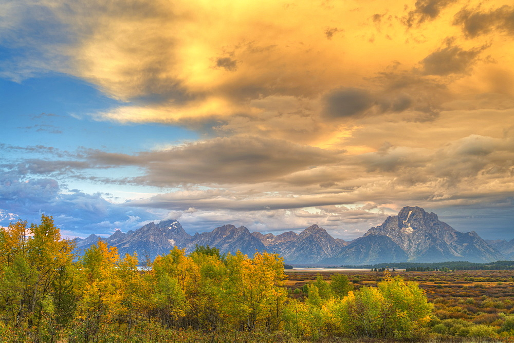 Glowing Golden Clouds Over Rugged Mountains In Grand Teton National Park, Wyoming, United States Of America