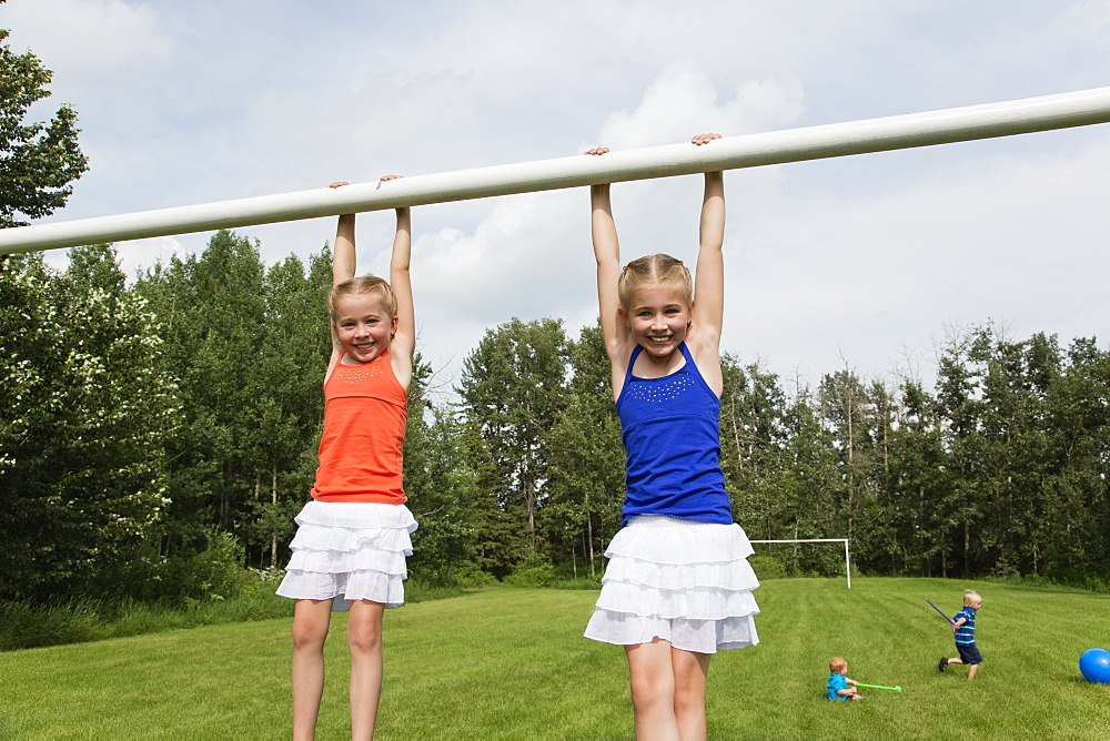Two Girls Holding Onto The Crossbar Of A Soccer Goal Post In A Park, Stony Plain, Alberta, Canada