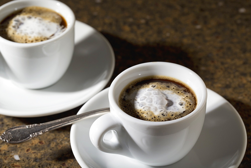 Close Up Of Two Espresso Coffee Cups And Saucers With Foam And Coffee On Granite Counter, Calgary, Alberta, Canada