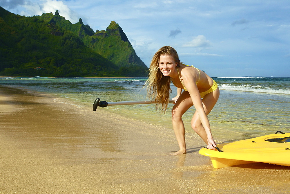 A Young Woman Pulls Her Stand Up Paddleboard Onto The Beach, Kauai, Hawaii, United States Of America