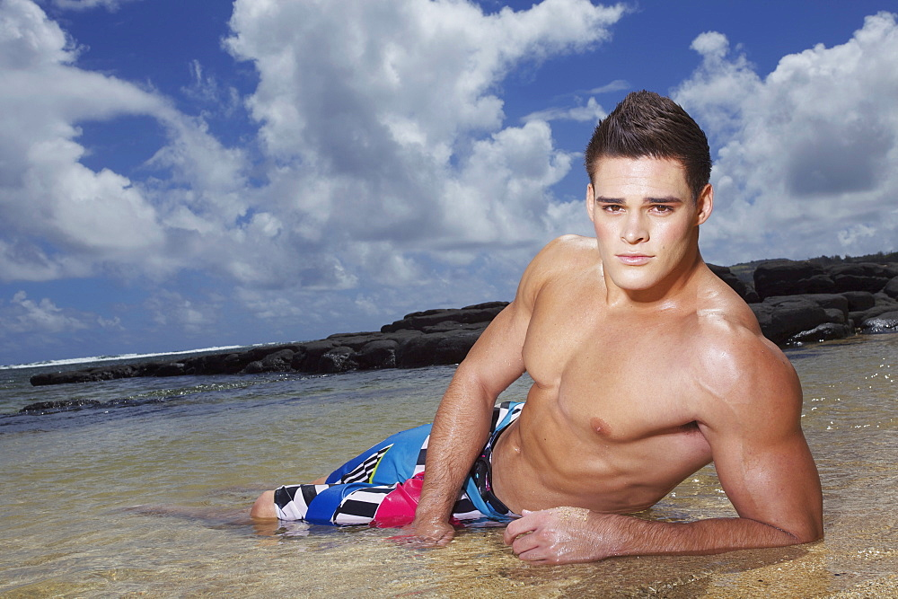A Young Man In A Bathing Suit Lays In The Shallow Ocean Water At The Beach, Hawaii, United States Of America