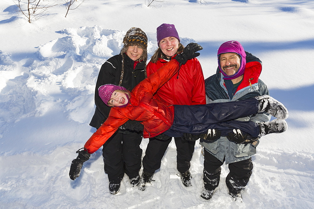 A Young Girl With Three Adults Playing In The Snow, Talkeetna, Alaska, United States Of America