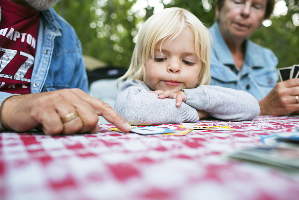 Grandparents Teaching A Young Granddaughter How To Play A Card Game, Peachland, British Columbia, Canada