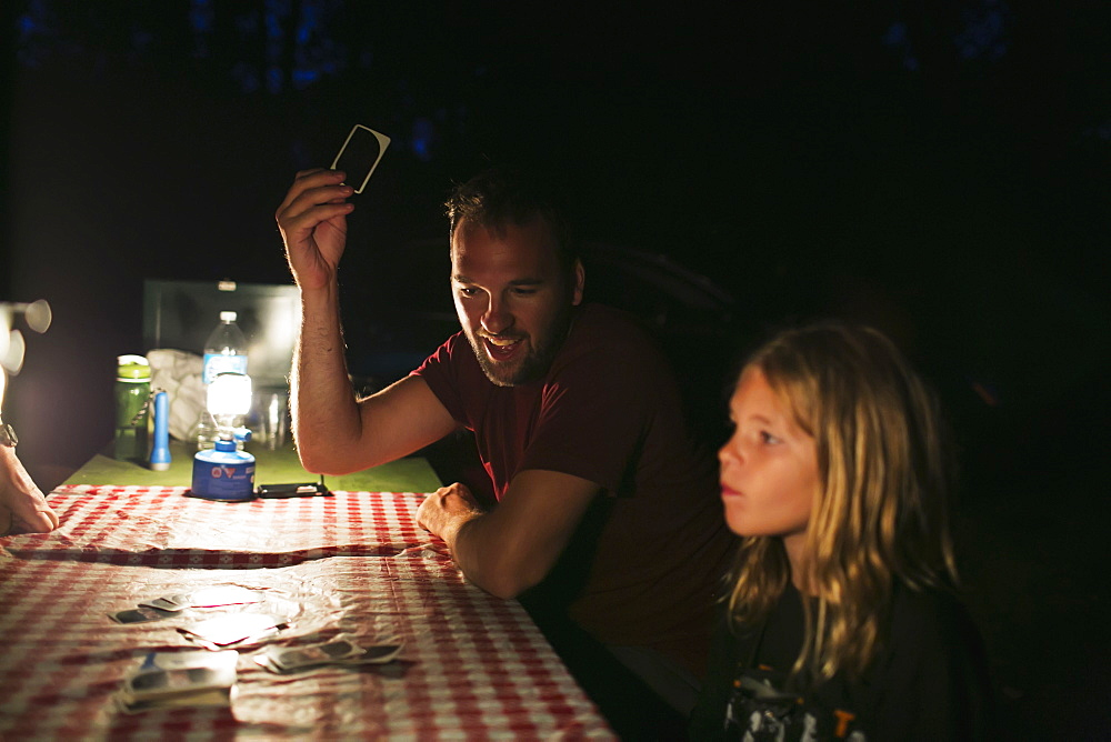 A Father And Daughter Playing Cards On A Picnic Table At Night By The Light Of A Lantern While Camping, Peachland, British Columbia, Canada