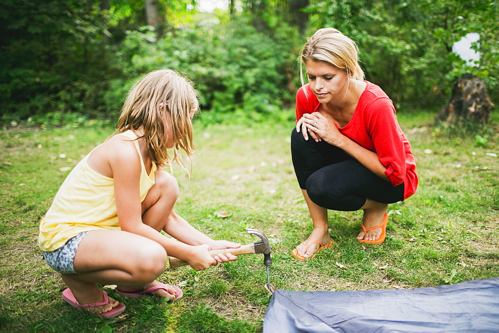 A Mother Watches Her Daughter Hammer In A Tent Peg, Peachland, British Columbia, Canada