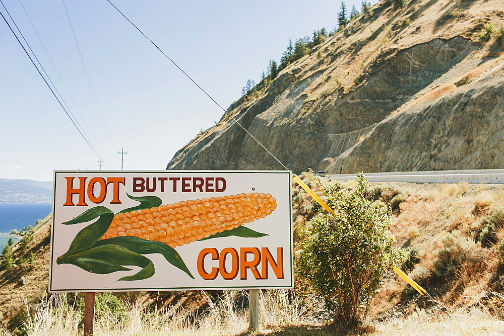 A Sign On The Roadside For Hot Buttered Corn, Peachland, British Columbia, Canada