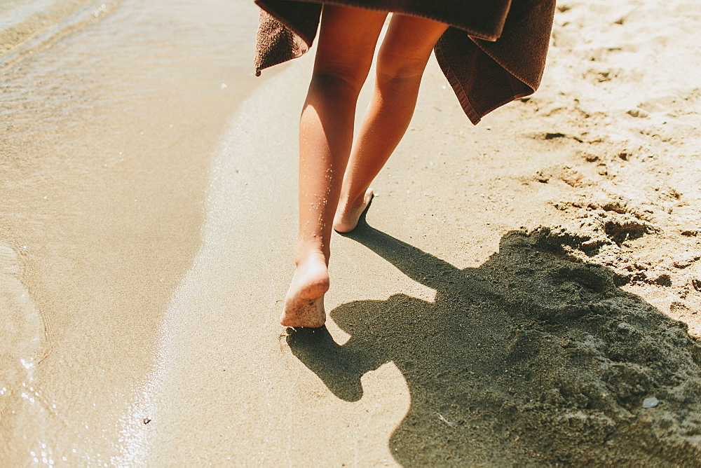 A Girl Walks Barefoot In The Sand Along The Water's Edge, Peachland, British Columbia, Canada