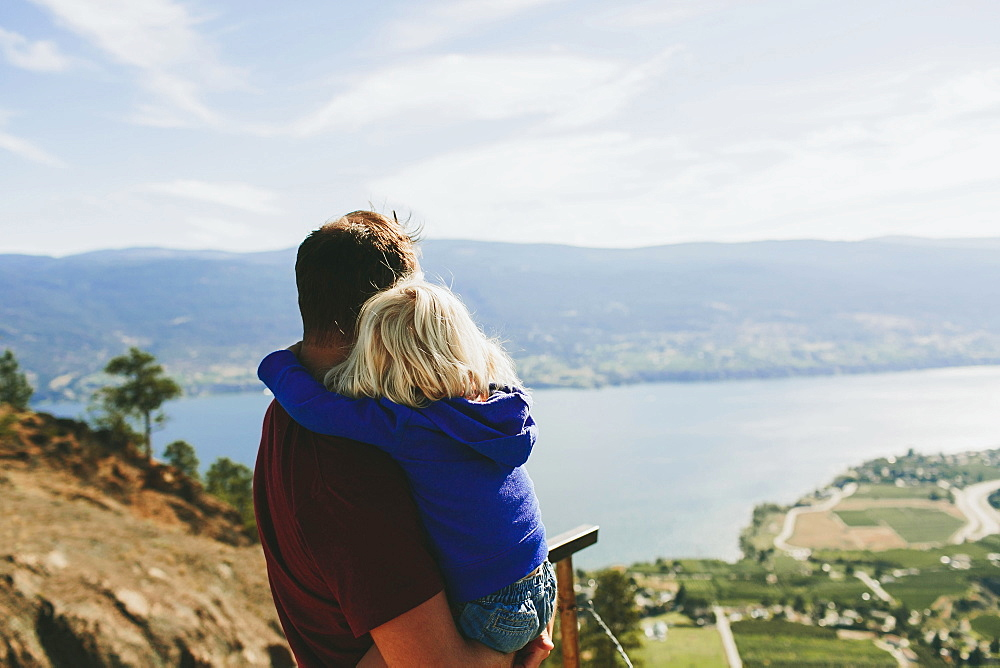A Father Holds His Young Daughter As They Look Out Over Lake Okanagan, Peachland, British Columbia, Canada