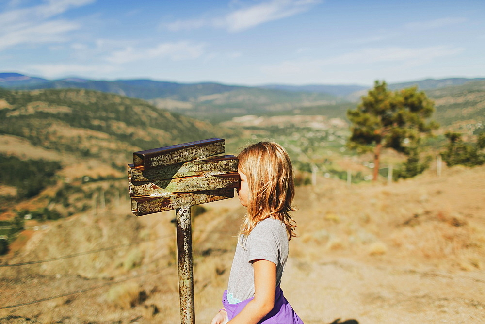 A Young Girl Looks Through An Old Rusty Set Of Binoculars, Peachland, British Columbia, Canada