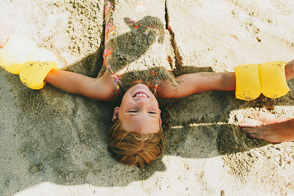 A Young Girl Being Buried In The Sand On The Beach, Peachland, British Columbia, Canada