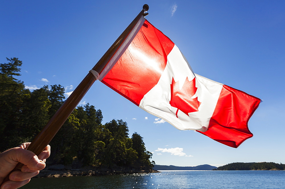 A Man Holds A Canadian Flag Into The Sun With The Gulf Islands The Distance, British Columbia, Canada