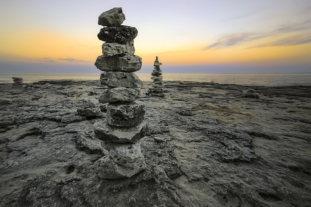 Rock Sculptures Dot The Shoreline As The Sun Dips Below The Horizon In Cave Point, Sturgeon Bay, Wisconsin, United States Of America