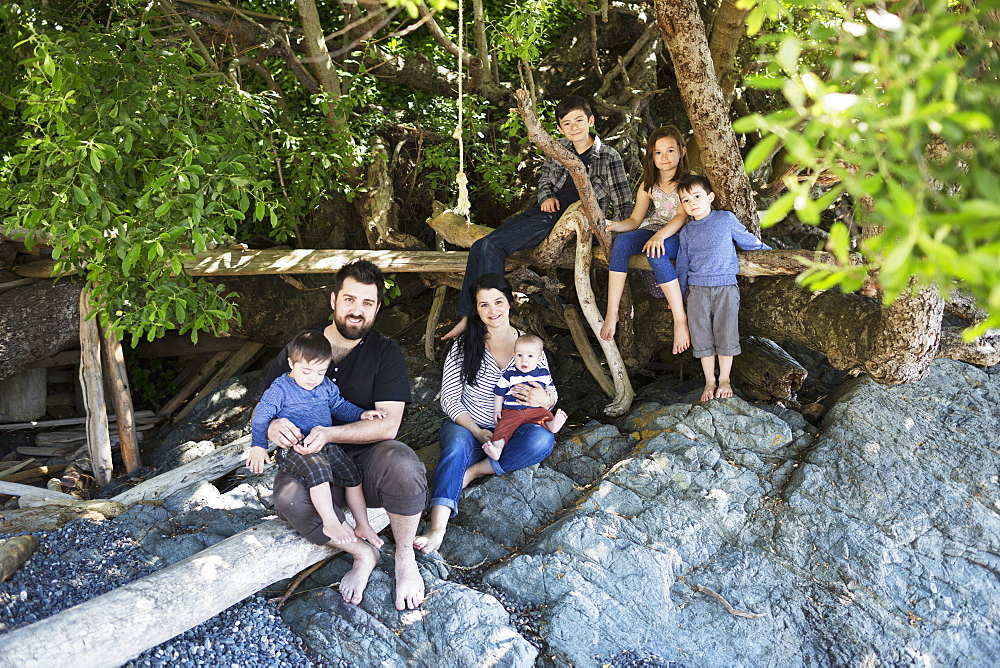 Portrait Of A Family Sitting On Large Rocks, Victoria, British Columbia, Canada