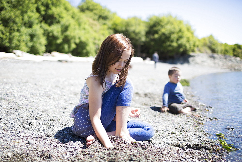 A Brother And Sister Sit In The Sand At The Water's Edge, Victoria, British Columbia, Canada