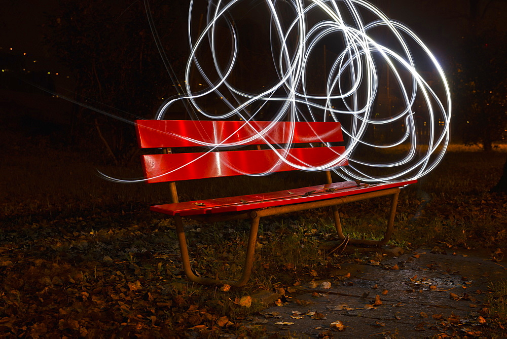 A Red Park Bench In Autumn With Swirls Of White Light In The Sky Around It, Locarno, Ticino, Switzerland