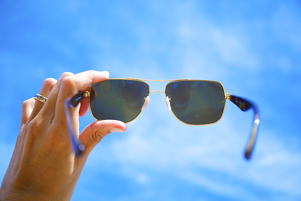 A Woman's Hand Holding Sunglasses To The Blue Sky With Sunlight, Kauai, Hawaii, United States Of America